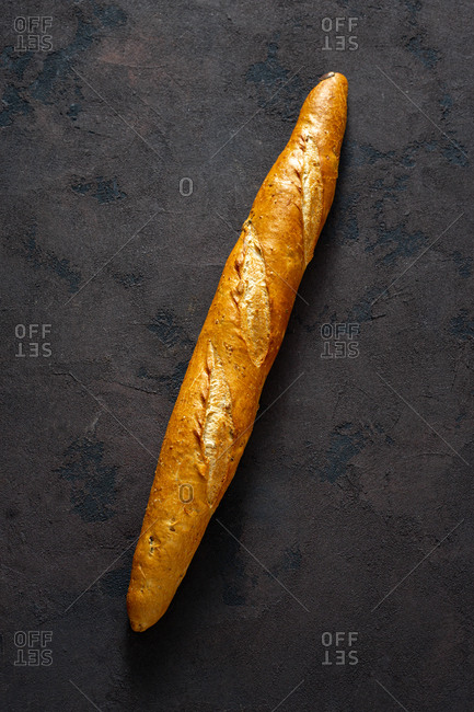 Overhead view whole baguette loaf on dark background