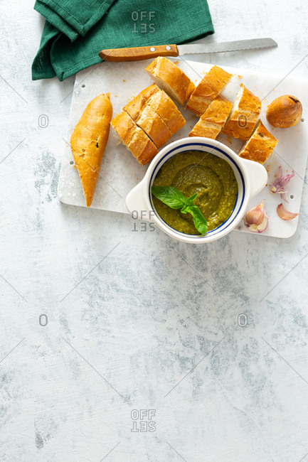 Homemade pesto sauce with fresh baguette on a white background