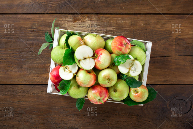 Red and green apples in wooden box on wooden table top view