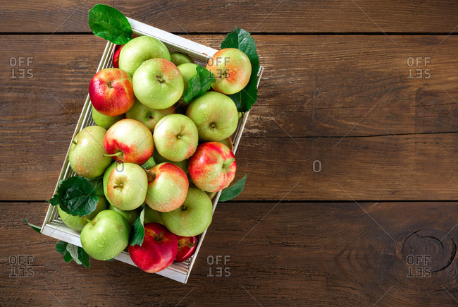 Red and green apples in wooden box on wooden table top view with copy space