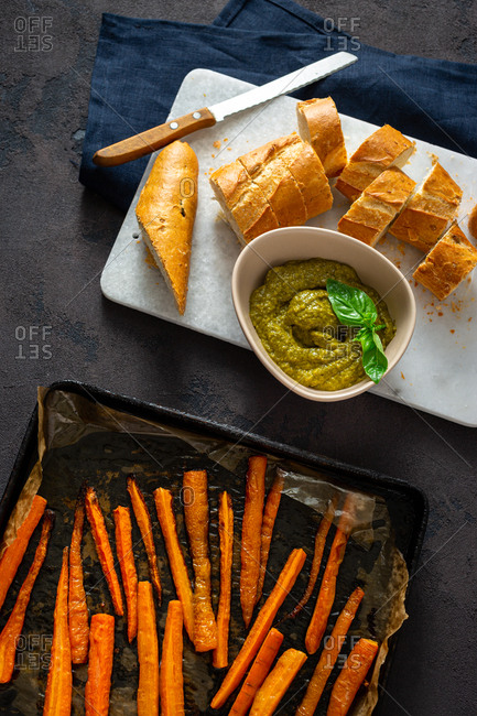 Overhead view cooking bruschetta with pesto sauce and baked carrots