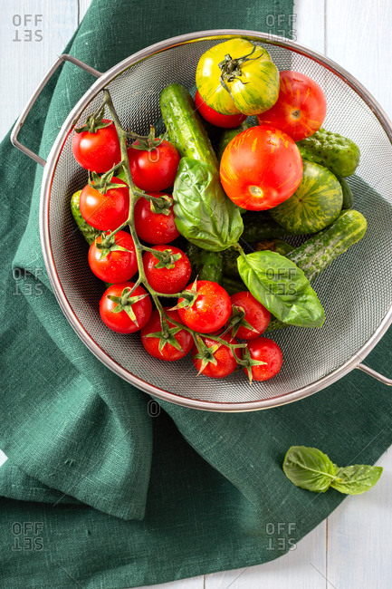 Washed basil with tomatoes in a sieve top view