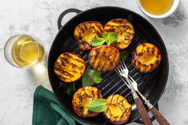 Peaches cooked in grill pan on a light background with glass of wine and honey top view