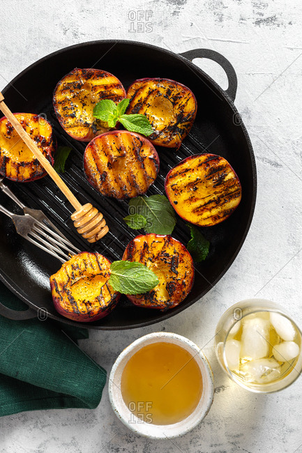 Grilled peach dessert on grill pan with cold tea and honey top view