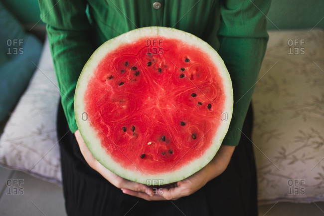 Woman holding a large half of a watermelon