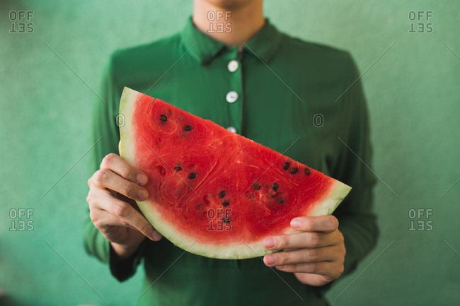 Woman in a green shirt holding a large slice of watermelon against a green background