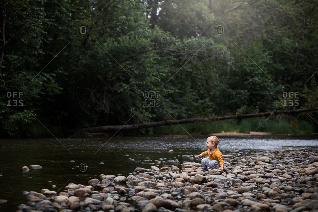 Little boy playing in stones on riverbank