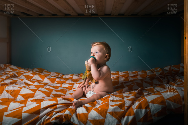 Baby boy sitting on bed sucking pacifier
