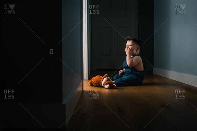 Baby boy sitting on hallway floor wearing overalls and hat