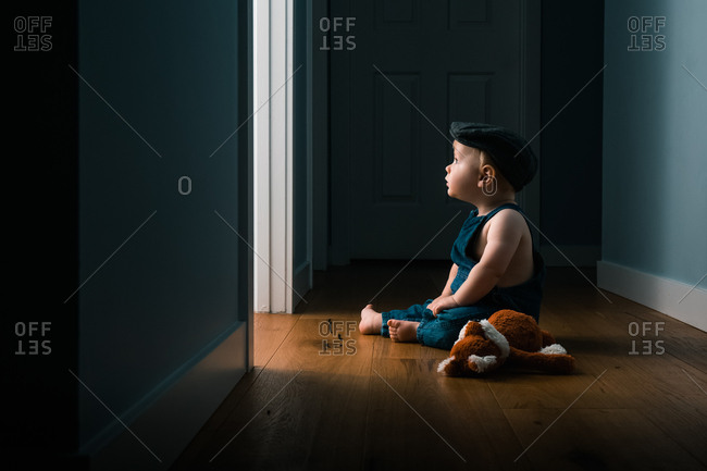 Baby sitting on hallway floor wearing overalls and hat