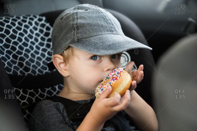 Toddler wearing baseball cap eating donut in car