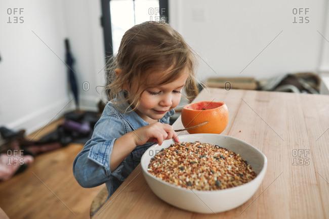 Toddler girl preparing a birdfeeder with a grapefruit