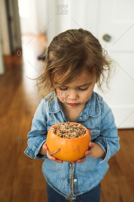 Toddler girl holding a homemade grapefruit birdfeeder