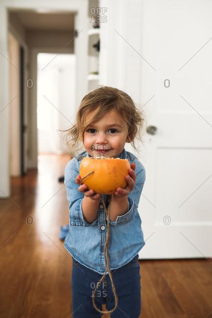 Smiling toddler girl holding a homemade grapefruit birdfeeder