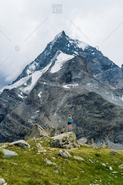 Woman hiking by snow-capped mountain