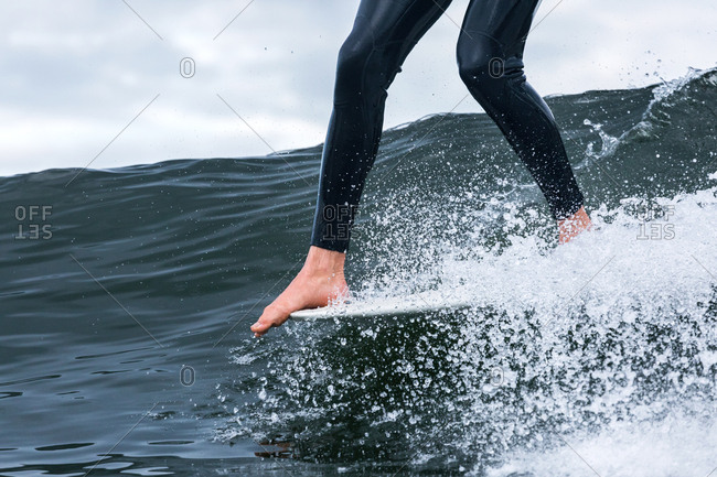 Feet of surfer on board riding a wave