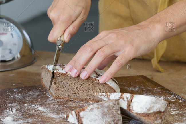 Person cutting artisan loaf of bread