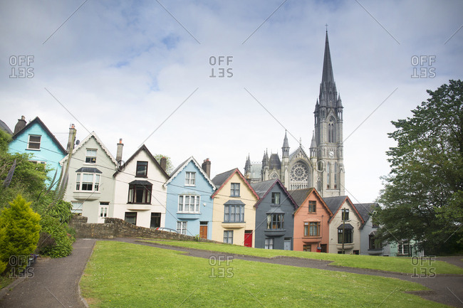 Cobh, Ireland - May 30, 2019: St Colman's cathedral behind row houses