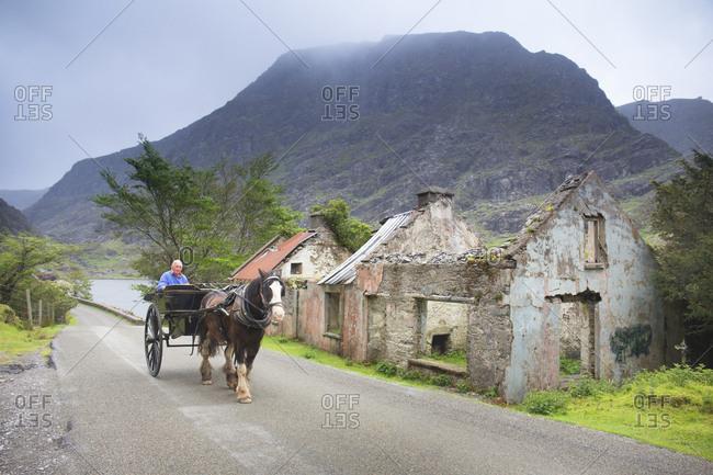 Killarney, County Kerry, Ireland - May 29, 2019: Horse cart driving by abandoned farmhouses in the Gap of Dunloe