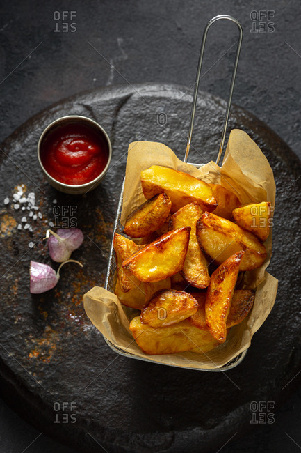 Fried potatoes in a basket with ketchup and garlic on a dark background close up