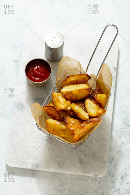 Fried potatoes in a basket with ketchup on a light background close up