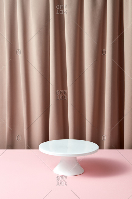 Porcelain cake stand with soft shadows on a pastel pink table