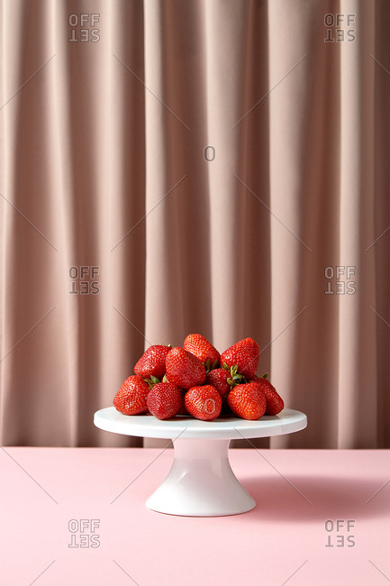 Delicious ripe strawberries on a white porcelain cake stand
