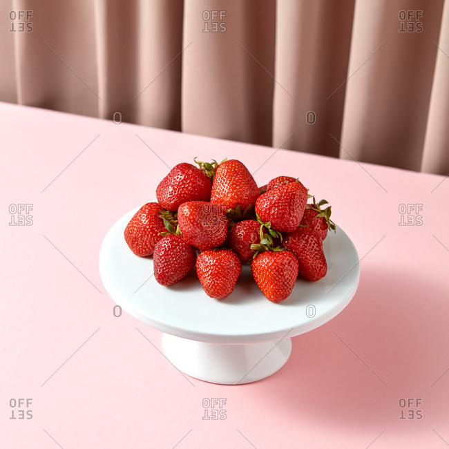Close up of delicious ripe strawberries on a white porcelain cake stand