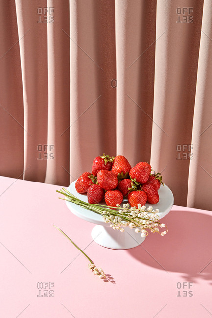 Freshly picked organic strawberries and spring flowers on a ceramic cake stand