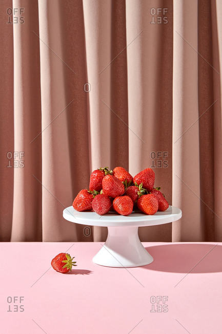 Organic freshly picked strawberries on a plate with shadow on a textile draped background.