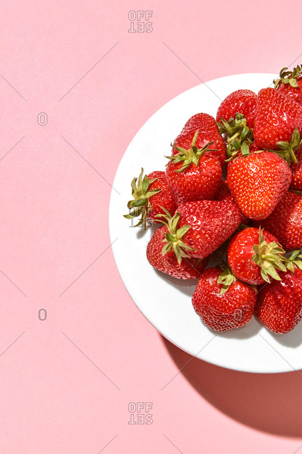 Tasty organic strawberries on a white porcelain plate against a pastel pink background