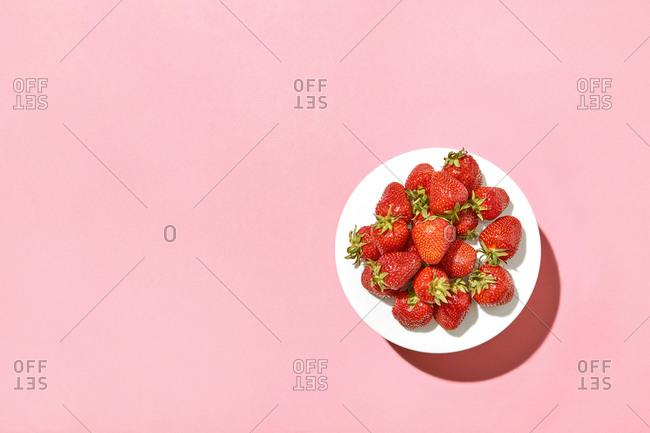 Delicious organic strawberries on a white porcelain plate against a pastel pink background