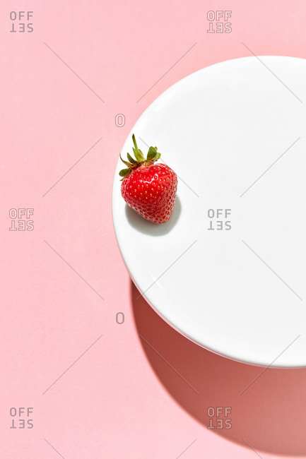 A strawberry on a white plate with hard shadows against a light pink background