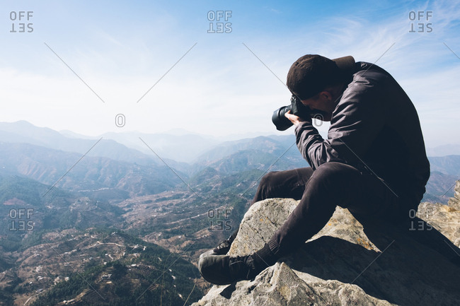Man photographing mountains from cliff