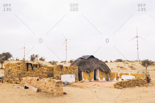 Thar Desert, India - July 28, 2019: Traditional huts by wind turbines in the desert