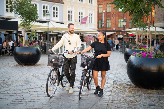 Couple walking bicycles in town