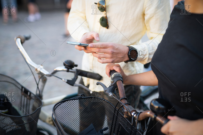Man showing woman cell phone while biking in town