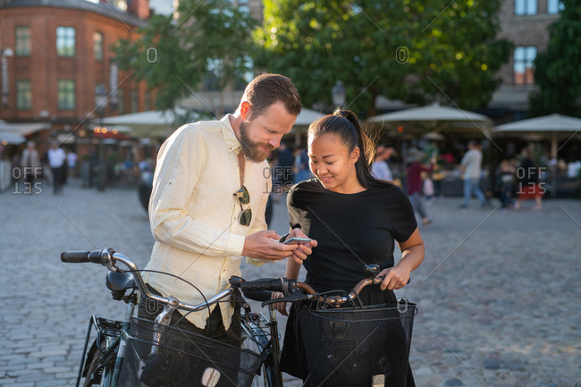 Man showing woman phone while biking in town