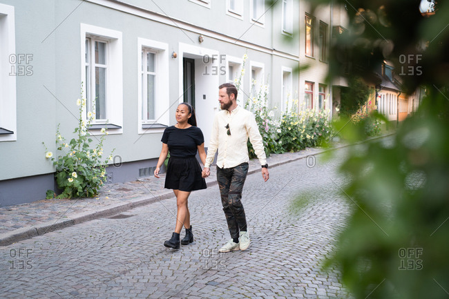 Couple walking down cobblestone street in town