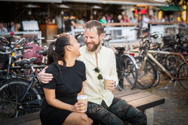Interracial couple enjoying coffee on outdoor bench