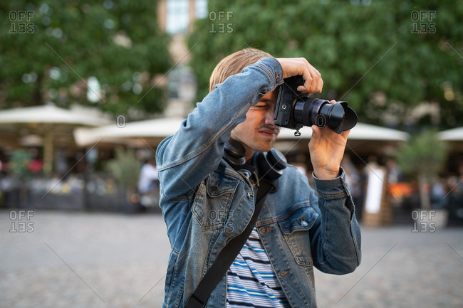 Man taking photographs with camera in town
