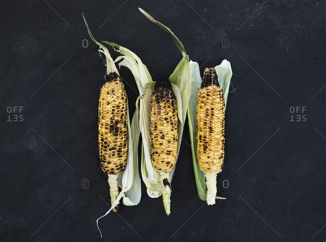 Grilled corn over black slate stone background