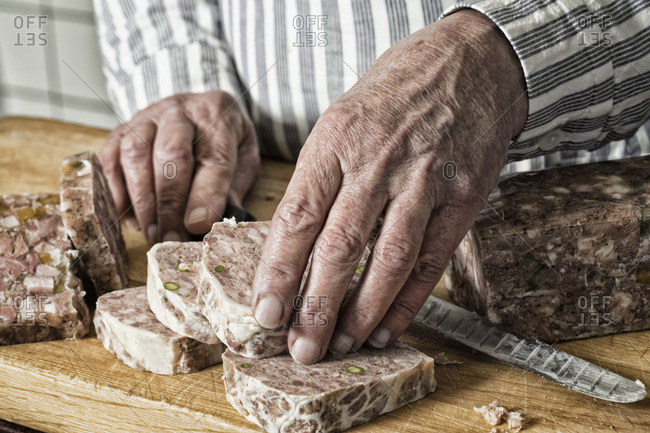 A man cutting pate into thick slices