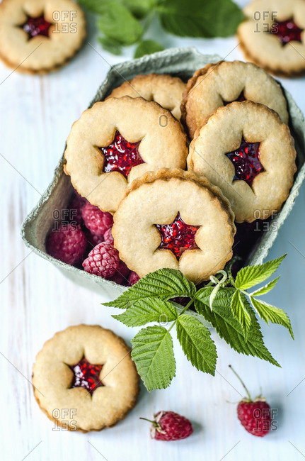 Linzer biscuits with raspberries on a blue surface
