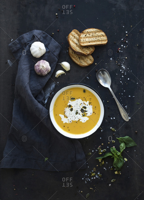 Pumpkin soup with cream, seeds, bread and fresh basil
