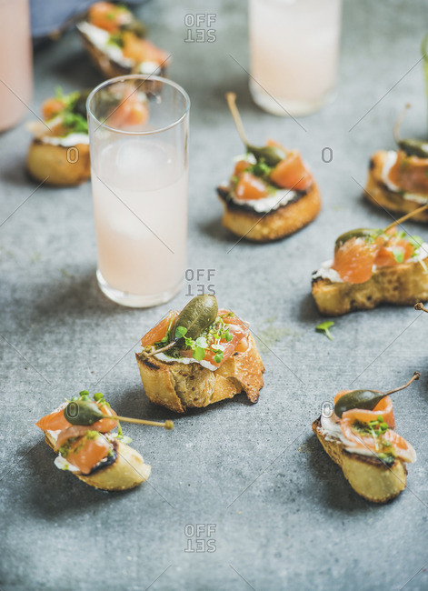 Party crostini with smoked salmon, pesto sauce, watercress and capers with pink grapefruit cocktails
