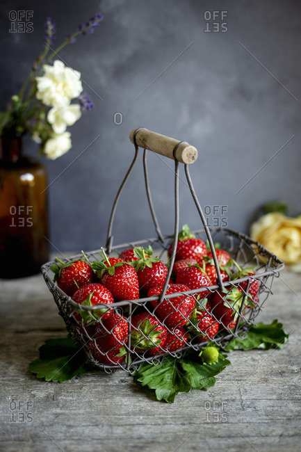 Fresh strawberries in a vintage wire basket on a dark surface