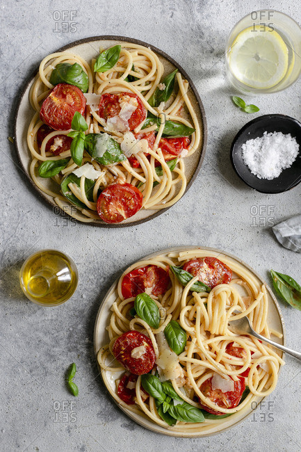 Two plates of bucatini pasta with roasted tomatoes and basil