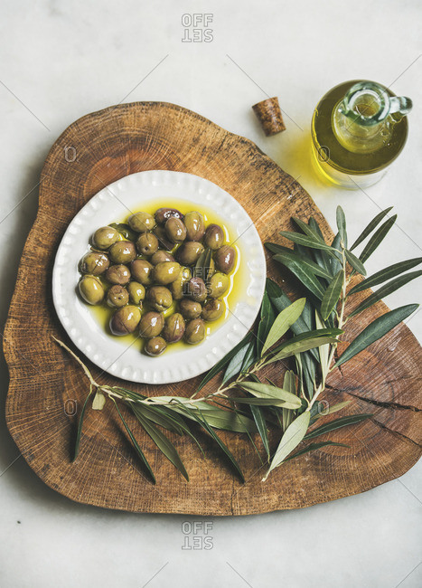 Pickled green Mediterranean olives and olive tree branch