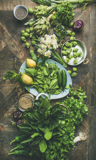Green vegetables, fruit, seeds, sprouts, flowers, greens over wooden background